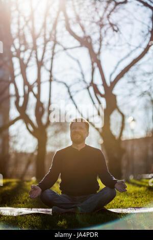 Homme mûr assis sur un tapis de yoga asana confortable en souriant et de détente dans parc. La méditation dans des Banque D'Images