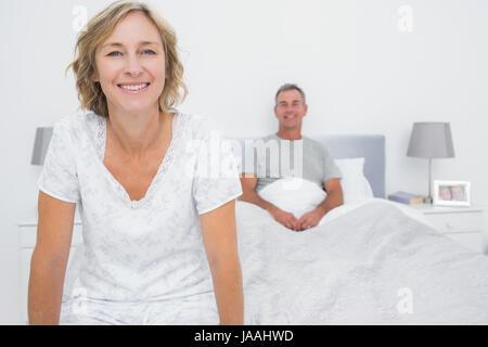 Heureux couple assis sur les extrémités opposées de bed smiling at camera dans la chambre à la maison Banque D'Images
