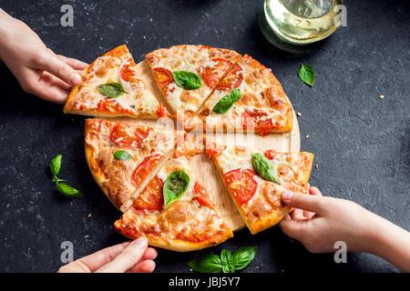 Les gens en tenant les mains des tranches de pizza Margherita. Pizza Margarita et mains close up sur fond noir. Banque D'Images