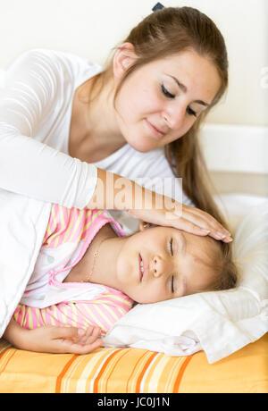 Portrait de mère tenant la main sur sa fille dormir avec soin Banque D'Images