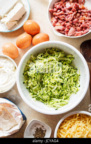 Frittata aux courgettes gâteau () ingrédients mélangés dans un bol blanc - les oeufs, la farine, la courgette râpée, Banque D'Images