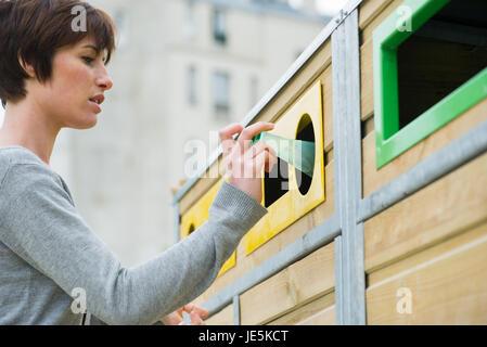 Mise en bouteille en plastique femme recycling bin Banque D'Images