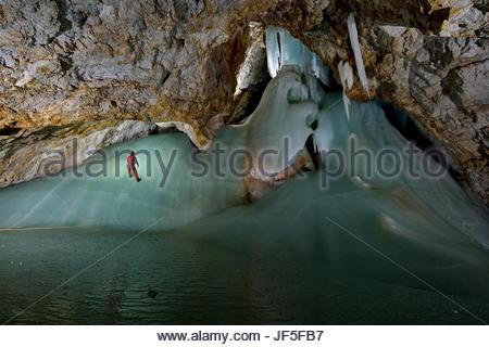 Un spéléologue rappels sur un terrain glissant la formation de glace dans Eiskogelhoehle, une des nombreuses grottes Banque D'Images