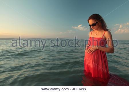 Portrait d'une femme enceinte debout dans l'eau au lac Balaton au coucher du soleil. Banque D'Images
