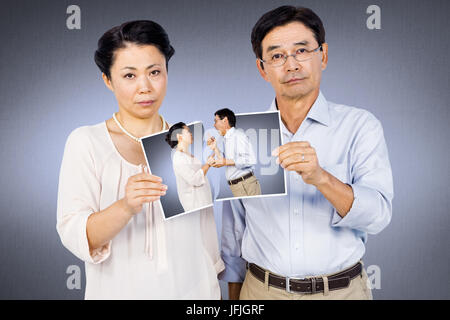 Composite image of asian woman holding a photo Banque D'Images
