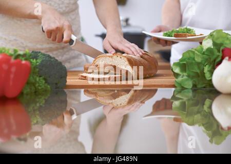 Close-up de la main de l'homme de trancher le pain dans une cuisine. Les amis de s'amuser tout en préparant une Banque D'Images