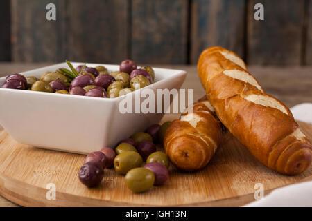 Les olives dans des contenants de pain sur une planche à découper Banque D'Images