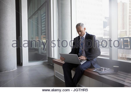 Businessman using laptop on bench in office lobby Banque D'Images
