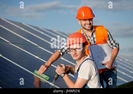 Les ingénieurs l'installation de panneaux solaires. Banque D'Images