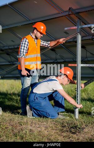 Les constructeurs d'installer le châssis avec des panneaux solaires sur pieu hélicoïde. Banque D'Images