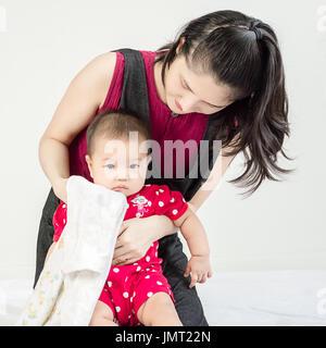 Lingettes mère un peu snivels adorable infant baby girl avec mouchoir de poche et à la recherche en appareil photo Banque D'Images