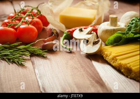 Les pâtes spaghetti aux tomates, basilic et fromage sur fond de bois rustique Banque D'Images