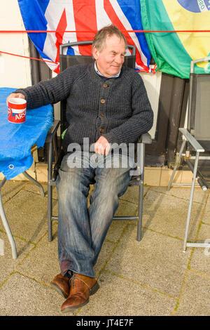 Senior male assis dehors un magasin tenant une chope dans ses mains, un jour d'hiver. Banque D'Images