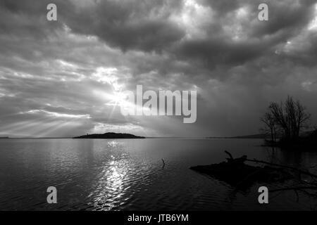 Les rayons du soleil émergeant dans les nuages au-dessus d'une île sur un lac, avec des arbres et des faisceaux Banque D'Images