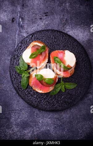 Crostini avec saumon, mozzarella, tomate et basilic. Démarreur ou apéritif italien Banque D'Images