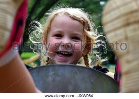 Smiling preschool girl swinging dans un parc Banque D'Images