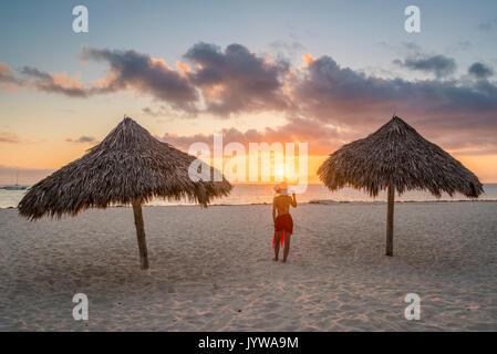 Bavaro Beach, Bavaro, Higuey, Punta Cana, République dominicaine. Femme par le chaume des parasols sur la plage Banque D'Images