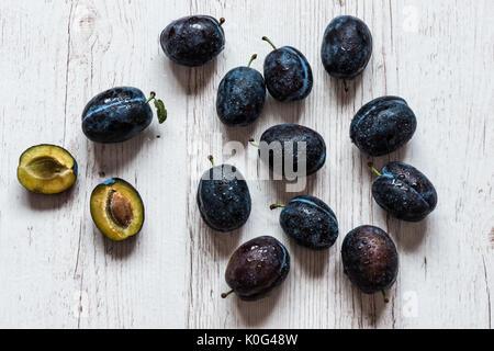Les prunes bleu gros plan sur un fond de bois blanc Banque D'Images