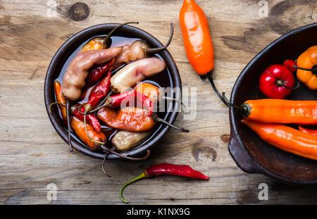 L'Amérique latine traditionnelle escabeche - piment fermentée. Piment épicé mariné au vinaigre. fond de bois Banque D'Images