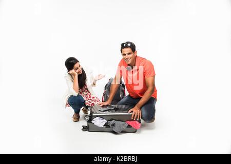Stock photo de jeunes indiens couple packing for holiday, essayant de fermer valise pleine de vêtements, isolé sur Banque D'Images