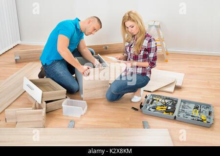 Portrait de jeune couple l'assemblage de tiroirs bois In New Home Banque D'Images