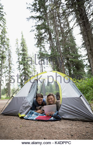 Teenage girl friends using digital tablet in camping tente Banque D'Images