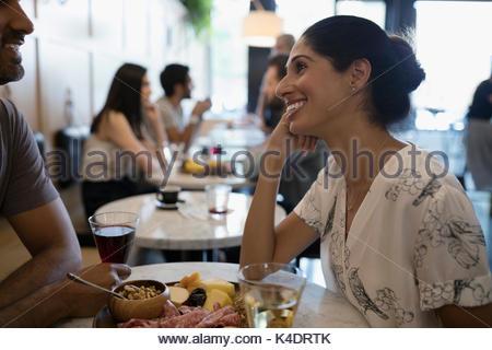 Woman smiling at petit ami, manger et boire du vin à table cafe Banque D'Images