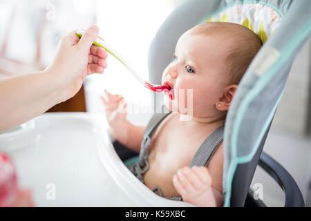 Mère nourrir bébé fille dans une chaise haute Banque D'Images