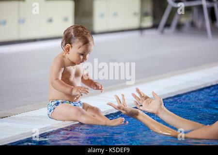 Jeune femme attraper petit fils assis au bord de la piscine intérieure Banque D'Images