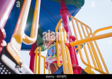 Un petit enfant fille joue à l'équipement de jeu sur une journée ensoleillée. Banque D'Images