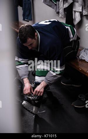 Joueur de hockey sur glace masculin de patinage de liage en position assise en dressing Banque D'Images