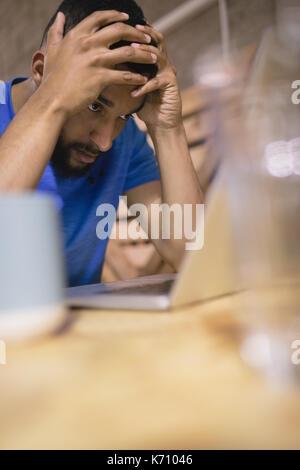 Jeune homme frustré avec laptop sitting at table in cafeteria Banque D'Images