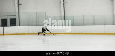 Joueur de hockey sur glace masculin pratiquant au rink Banque D'Images