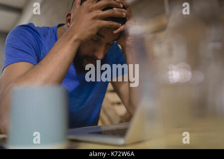Jeune homme frustré avec laptop sitting at table in cafe Banque D'Images