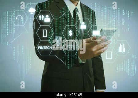 Businessman with fintech icône et internet des objets avec code matrice historique , d'investissement et de la technologie Banque D'Images