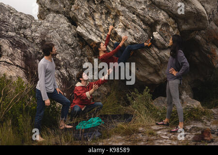 Les amis d'aider l'homme à l'escalade sur une journée ensoleillée Banque D'Images