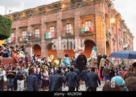 Une fanfare suit un défilé de marionnettes de papier mâché géant appelé mojigangas dans une procession à travers Banque D'Images