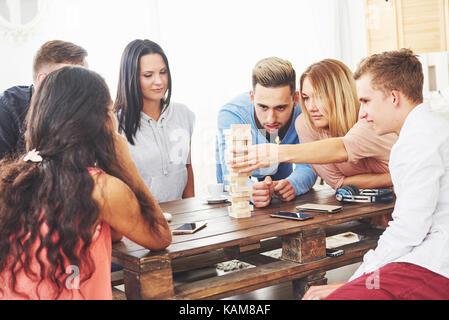 Groupe d'amis créatifs assis à table en bois. Les gens s'amuser tout en jouant jeu Banque D'Images