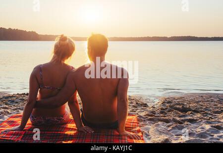 Couple romantique sur la plage au coucher de soleil colorés sur fond de Banque D'Images