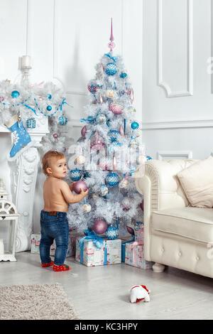 Baby Girl, debout près de l'arbre de Noël et décorations holding Banque D'Images