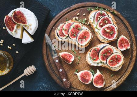 La bruschetta avec des figues violettes, ricotta et miel sur planche à découper en bois servi avec fromage brie Banque D'Images