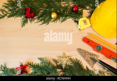 Casque de protection, mason outils et décorations de Noël sur fond de bois Banque D'Images