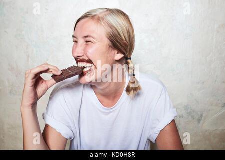 Woman eating barre de chocolat, du chocolat autour de la bouche, laughing Banque D'Images