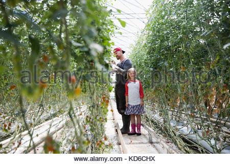 Père et fille le jardinage, contrôler la culture plants in greenhouse Banque D'Images