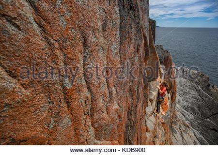 Rock climber au cours trad escalade dans le parc national de Freycinet. Banque D'Images