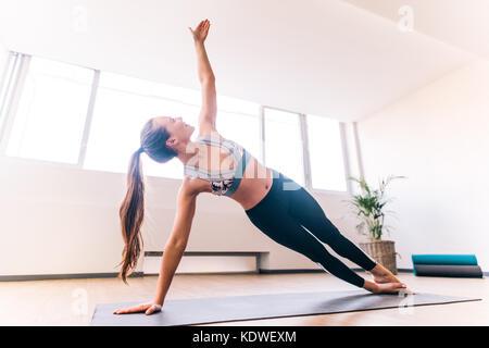 Femme Slim en planche à côté de yoga, Vasisthasana exercice. Femme en équilibre sur mat à l'intérieur à la salle Banque D'Images