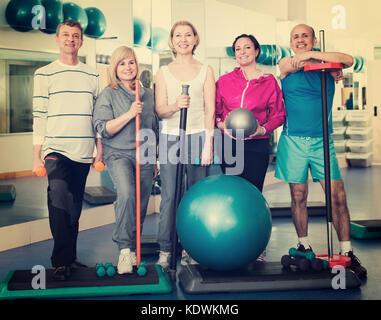 Groupe d'hommes et de femmes matures joyeux après l'exercice dans la salle de sport avec équipements de sport Banque D'Images