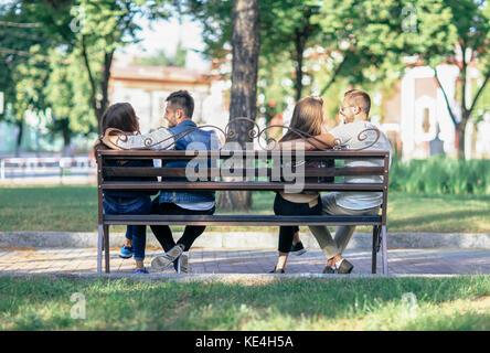 Deux amoureux des couples assis sur des extrémités d'un banc. les jeunes heureux les hommes et les femmes communiquent Banque D'Images