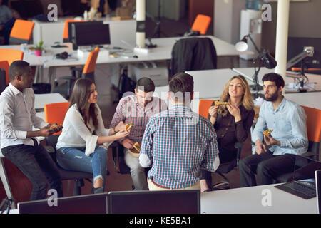Groupe de jeunes dans un bureau moderne et de réflexion de la réunion de l'équipe ont tout en travaillant sur les Banque D'Images