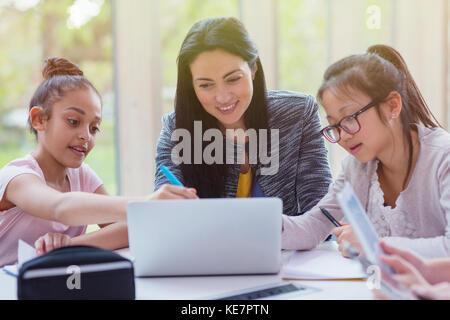 Enseignante et les filles à la recherche ordinateur portable dans la bibliothèque Banque D'Images